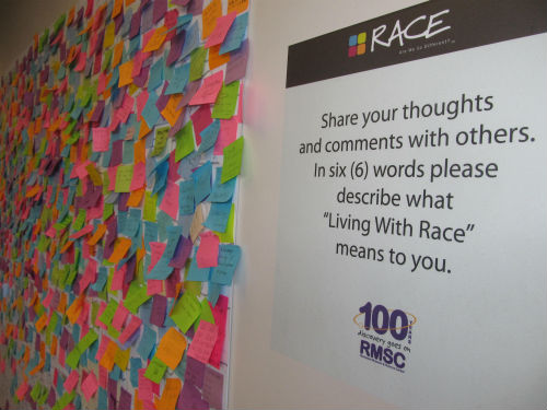 "The Rochester Museum & Science Center hosted an early 2013 touring exhibition called Race: Are We So Different? The center created this board in the lobby outside the exhibit for visitors to describe ""Living with Race"" in six words. The posts were placed on a world map mural that filled a large wall."